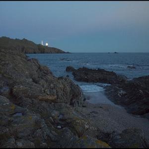 Full moon rising behind Start Point Lighthouse
