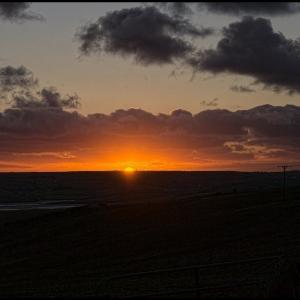 The sun sinks below the wide horizon